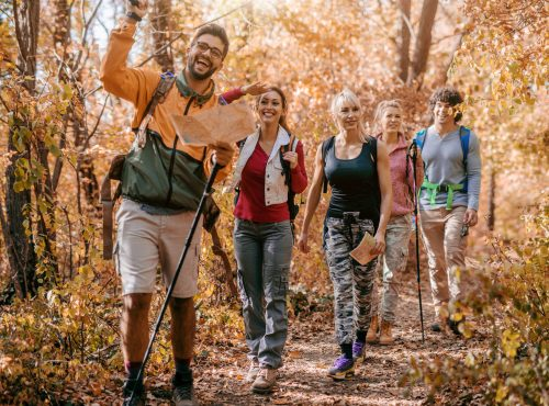 Man holding map and showing other hikers right way while walking in woods.Autumn season. Adventure concept.