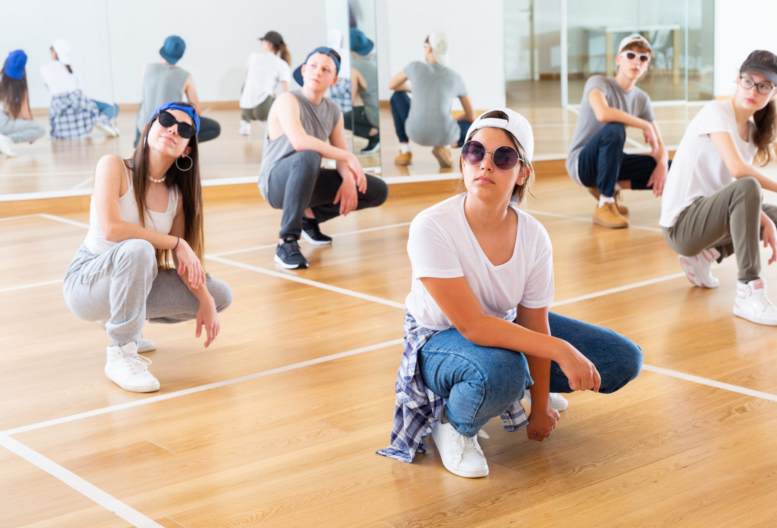 Group of teenagers in casual clothes training hip-hop in class, learning modern dance movements